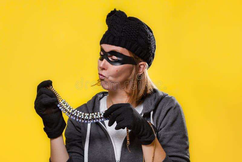 El concepto de robo Una mujer con sombrero, máscara y guantes sostiene las joyas en ambas manos y las examina Fondo amarillo y imágenes de archivo libres de regalías