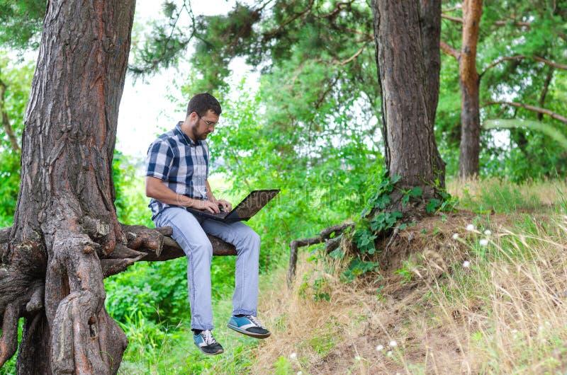 El concepto de trabajo remoto: un hombre joven con un ordenador portátil se sienta en el th fotografía de archivo