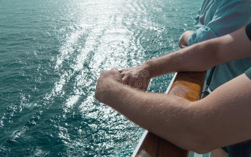 El concepto de travesías del mar Las manos de los hombres en la verja del barco de cruceros en el fondo de las ondas y de la pues imágenes de archivo libres de regalías