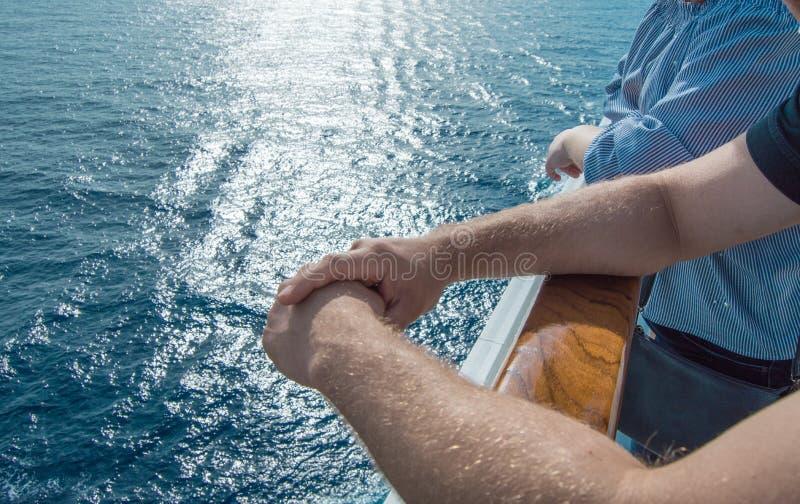 El concepto de travesías del mar Las manos de los hombres en la verja del barco de cruceros en el fondo de las ondas y de la pues fotos de archivo
