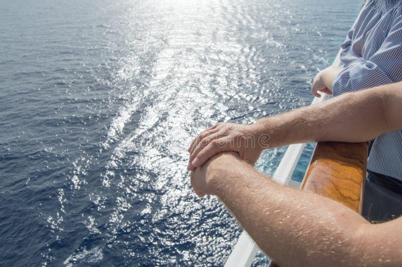 El concepto de travesías del mar Las manos de los hombres en la verja del barco de cruceros en el fondo de las ondas y de la pues foto de archivo libre de regalías