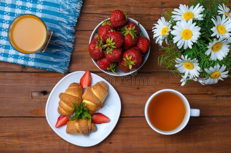 El concepto de un desayuno romántico: cruasanes con el strawberrie fotografía de archivo
