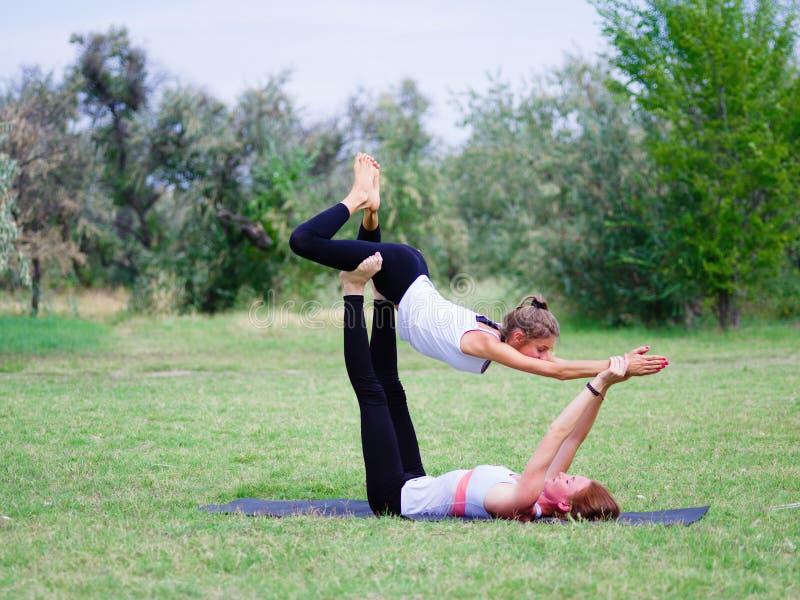 El concepto de una forma de vida sana Dos mujeres que hacen yoga en el parque imagen de archivo