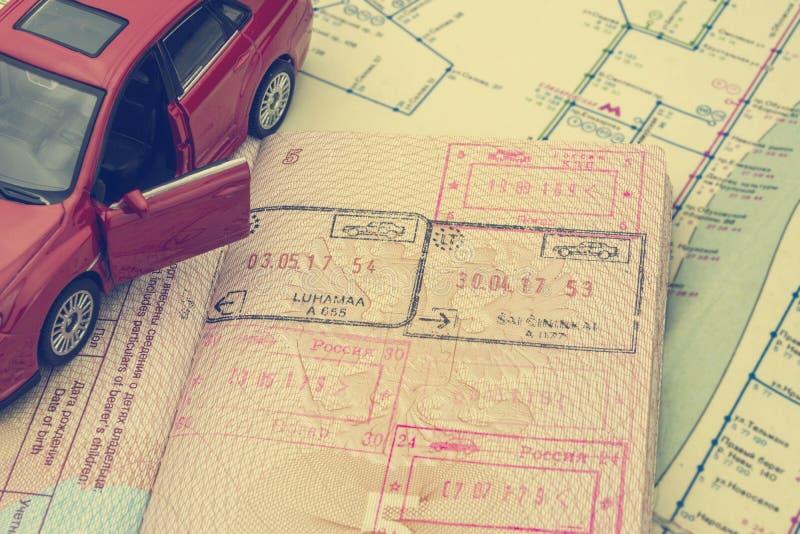El concepto de viaje en coche: el pasaporte con los sellos de la frontera Correspondencia de la ciudad Modelo rojo del coche Proc foto de archivo libre de regalías