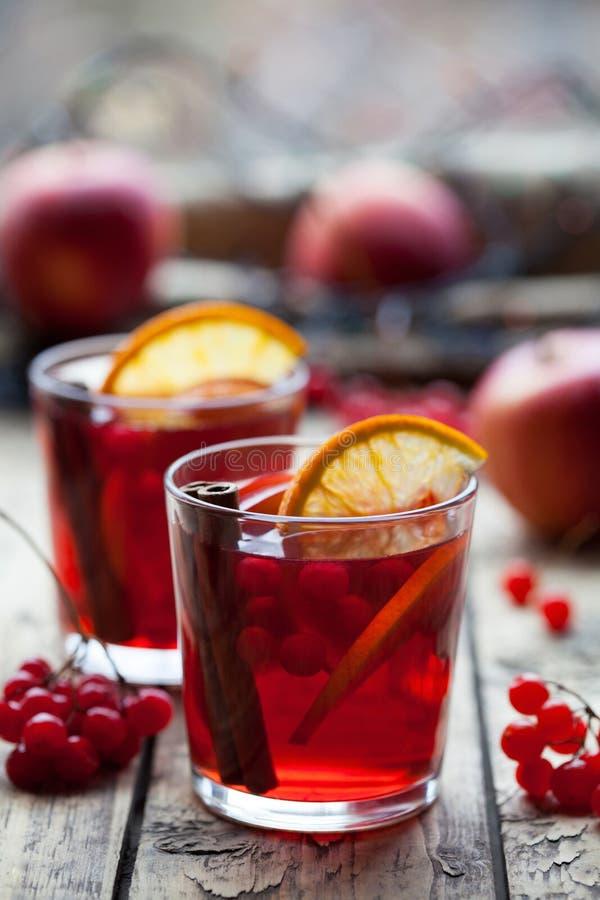 El concepto de vino reflexionado sobre hecho en casa Sangría o sacador con la naranja, la manzana y las bayas en un vidrio en la  foto de archivo