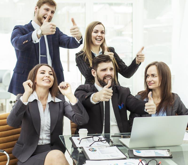 El concepto del éxito en equipo favorable a la actividad empresarial del negocio hace un gesto de pulgares para arriba imágenes de archivo libres de regalías