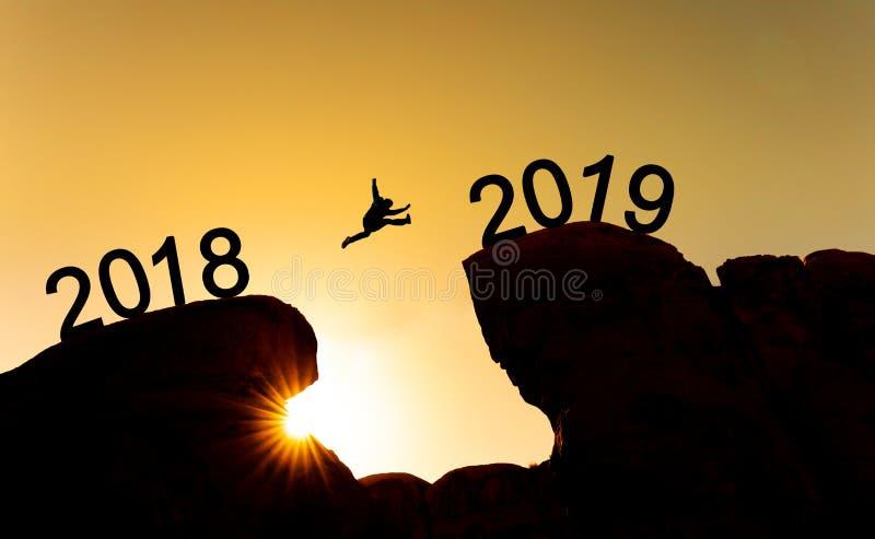 El concepto del Año Nuevo, siluetea a un hombre que salta a través del acantilado a partir de 2018 a 2019 foto de archivo