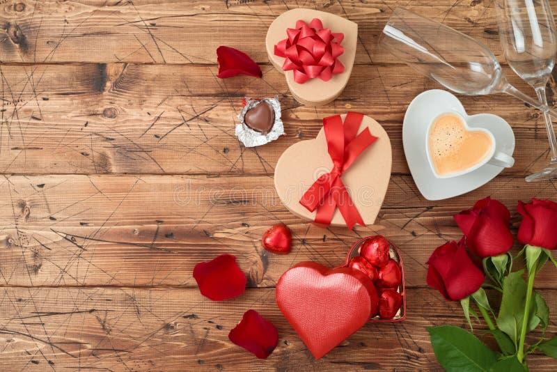 El concepto del día de tarjeta del día de San Valentín con la taza de café, chocolate de la forma del corazón, subió las flores y imagenes de archivo