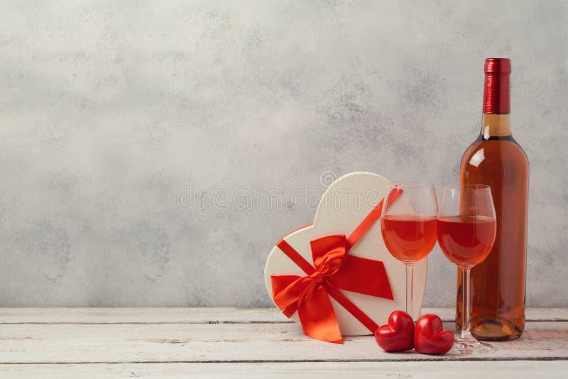 El concepto del día de tarjetas del día de San Valentín con los pares de copas de vino y el corazón forman la caja de regalo fotos de archivo