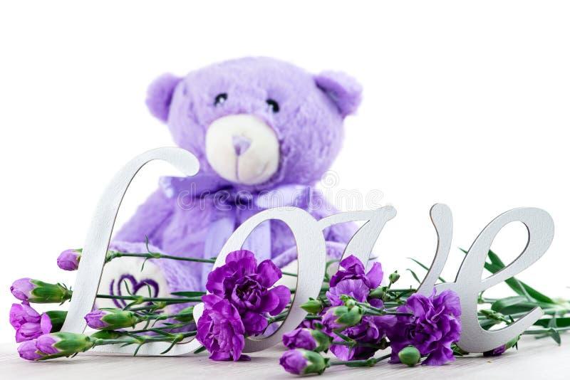 El concepto del día del ` s de la tarjeta del día de San Valentín con el oso del juguete, letras ama y florece, foto de archivo