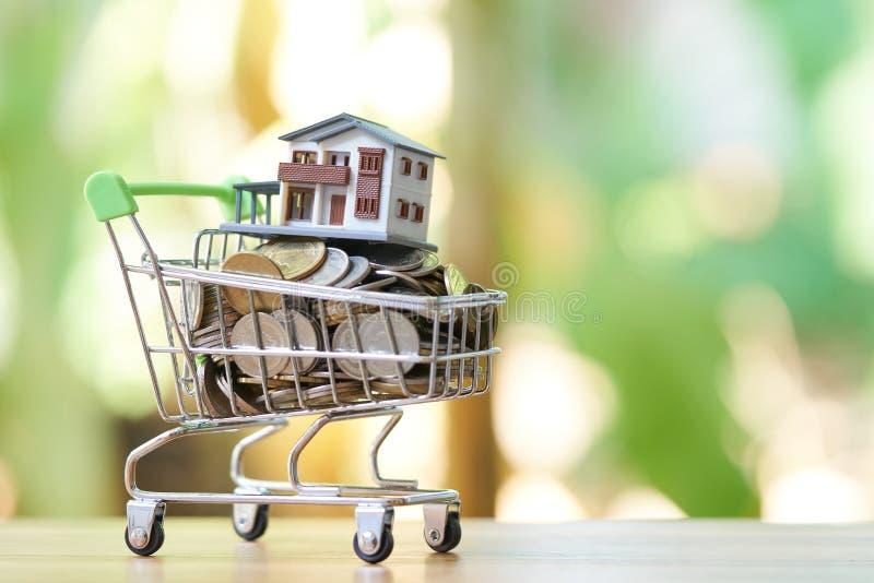 El concepto del dinero del ahorro de recogida acuña el dinero tailandés en un modelo del carro de la compra y de la casa en fondo foto de archivo