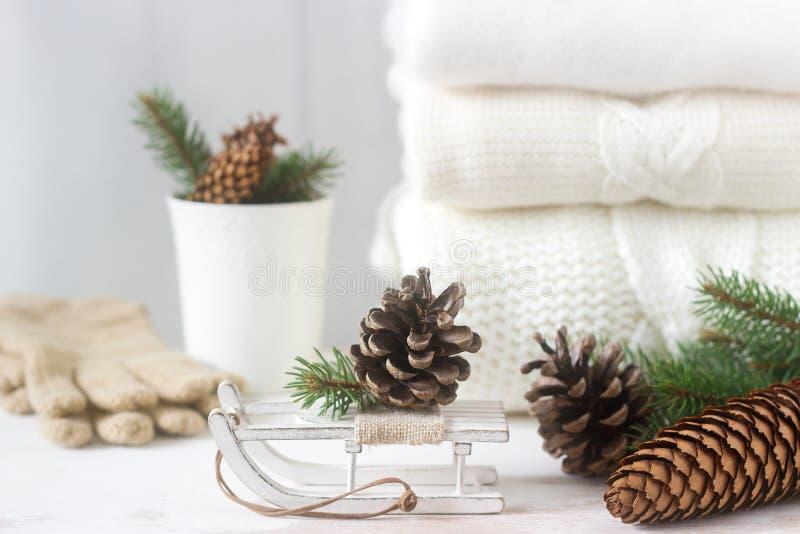El concepto del invierno con el jersey, los guantes, los trineos, la taza, los conos y el abeto combinados blancos ramifica foto de archivo