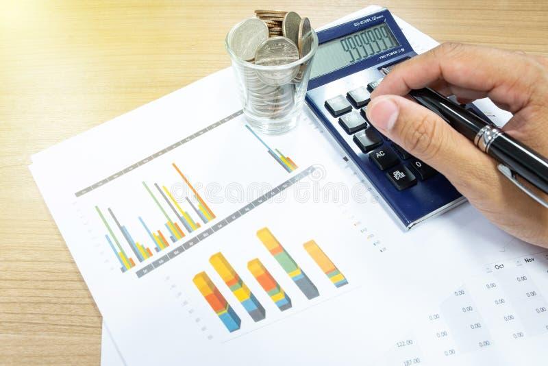 El concepto del negocio de hombre de negocios utiliza una calculadora para calcular imágenes de archivo libres de regalías