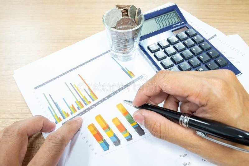 El concepto del negocio de hombre de negocios utiliza una calculadora para calcular imagenes de archivo