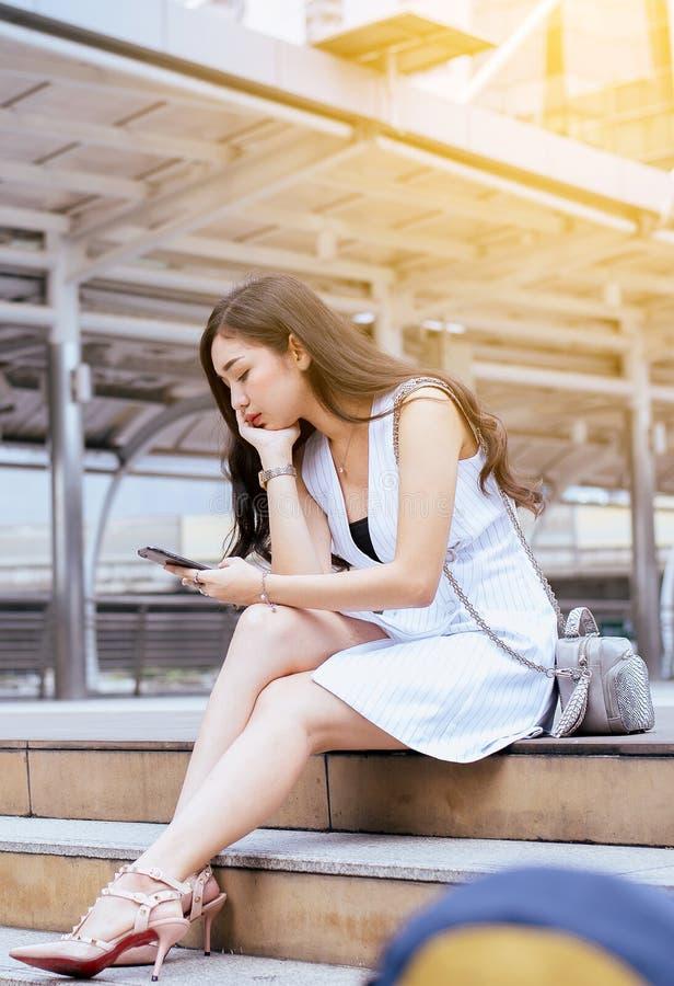 El concepto del problema de desempleo, mujer hermosa asiática subrayó y depresión del trabajo mientras que se sentaba al aire lib foto de archivo