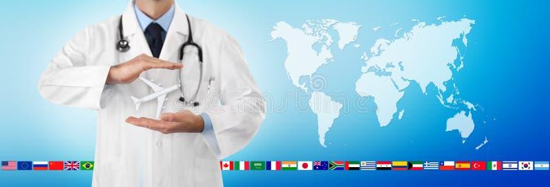 El concepto del seguro médico del viaje, las manos del doctor protege un aeroplano en fondo azul con las banderas en mapa del mun fotografía de archivo libre de regalías