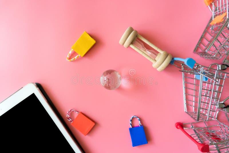El concepto en línea shoping mínimo, el panier de papel colorido y la carretilla van abajo de flotar el backgroundp rosado imágenes de archivo libres de regalías
