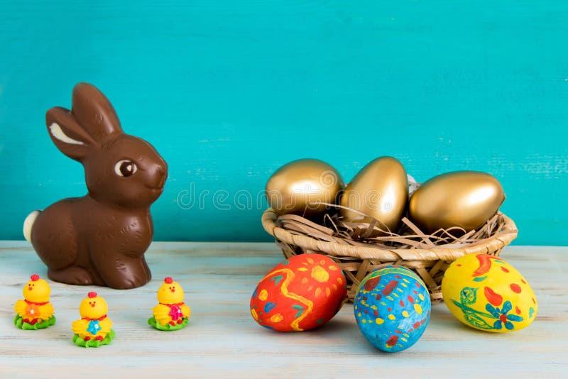 El concepto feliz de Pascua con el aster del oro del ANG del color eggs en cesta al lado del conejito de pascua del chocolate y p imagen de archivo libre de regalías