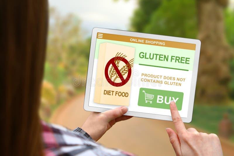 El concepto libre de la dieta del gluten, muchacha sostiene la tableta digital en fondo borroso de la naturaleza fotografía de archivo