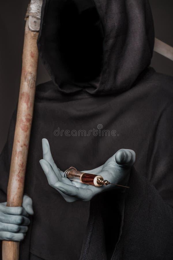 El concepto: matanza de las drogas Parca que sostiene la jeringuilla con las drogas foto de archivo