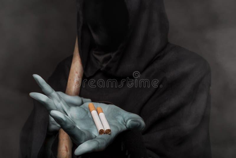 El concepto: matanzas que fuman Ángel de la muerte que sostiene el cigarrillo imágenes de archivo libres de regalías