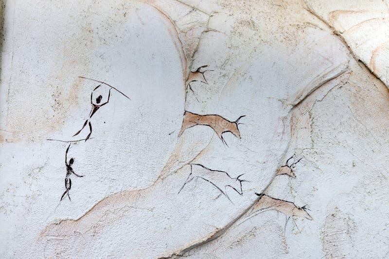 El concepto pintado en una roca, gente antigua caza el búfalo animal con una lanza imagenes de archivo