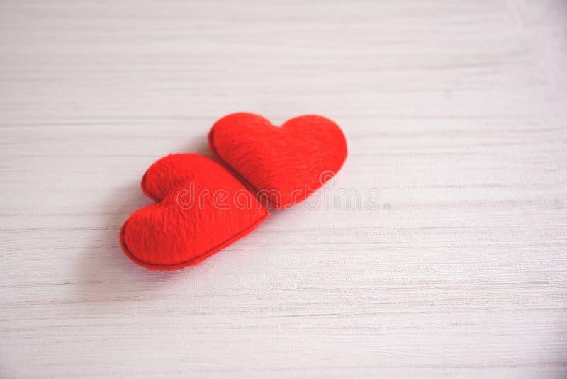 El concepto romántico del corazón del amor de día de San Valentín junta el corazón rojo adornado en el fondo de madera blanco de  imagen de archivo libre de regalías