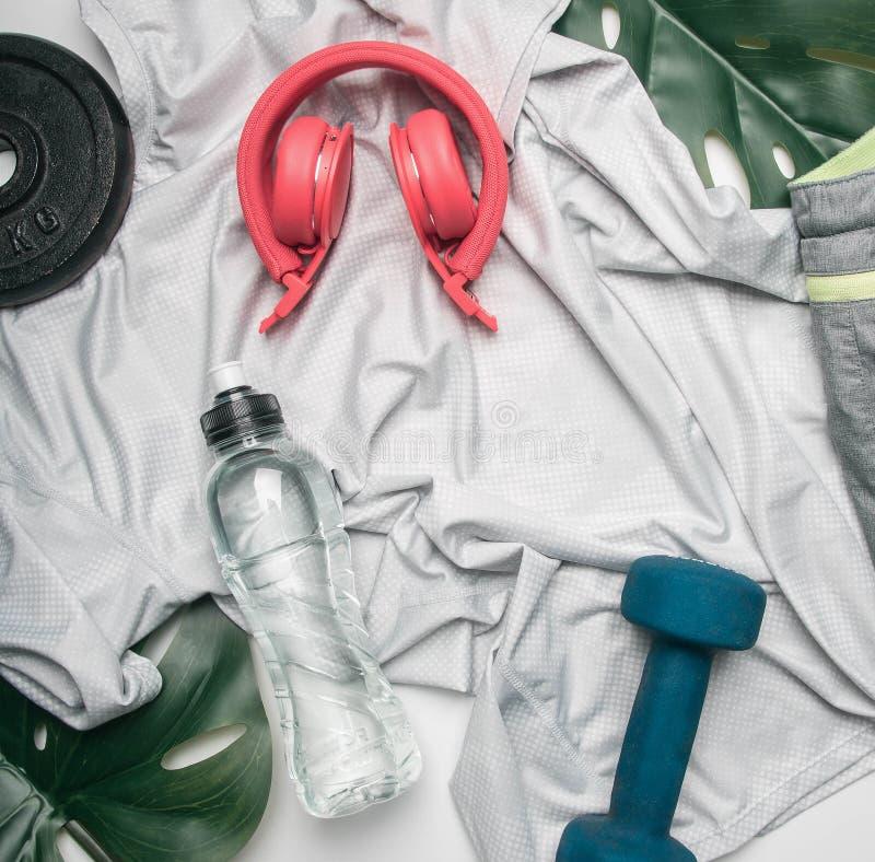 El concepto se divierte la forma de vida, ropa de deportes, auriculares, pesas de gimnasia, alineadas en un fondo blanco, con un  foto de archivo