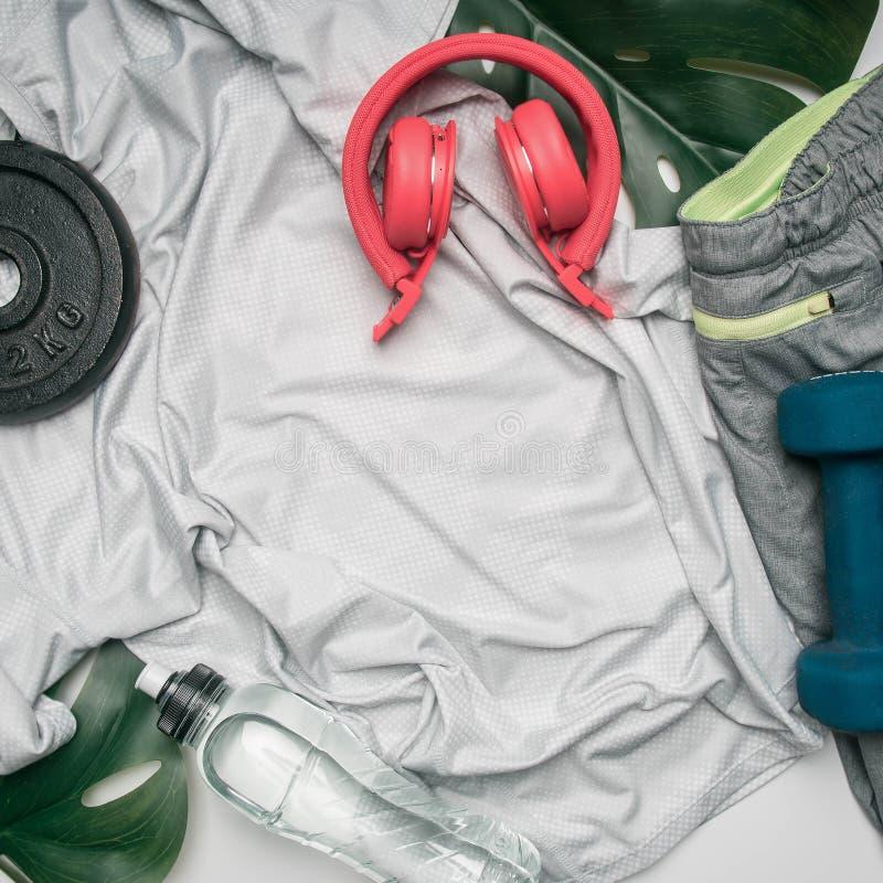 El concepto se divierte la forma de vida, ropa de deportes, auriculares, pesas de gimnasia, alineadas en un fondo blanco, con la  imagenes de archivo