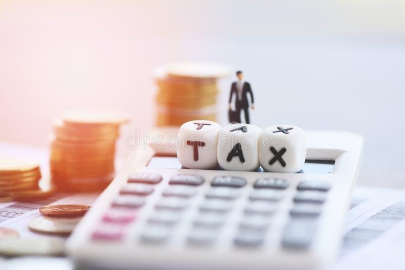 El concepto y la calculadora del impuesto apilaron monedas en el papel de la cuenta de la factura para el pago pagado de relleno  foto de archivo