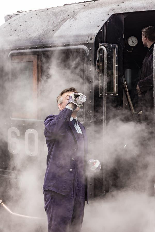 El conductor británico del tren del vapor bebe el agua en Nene Valley Railway fotografía de archivo