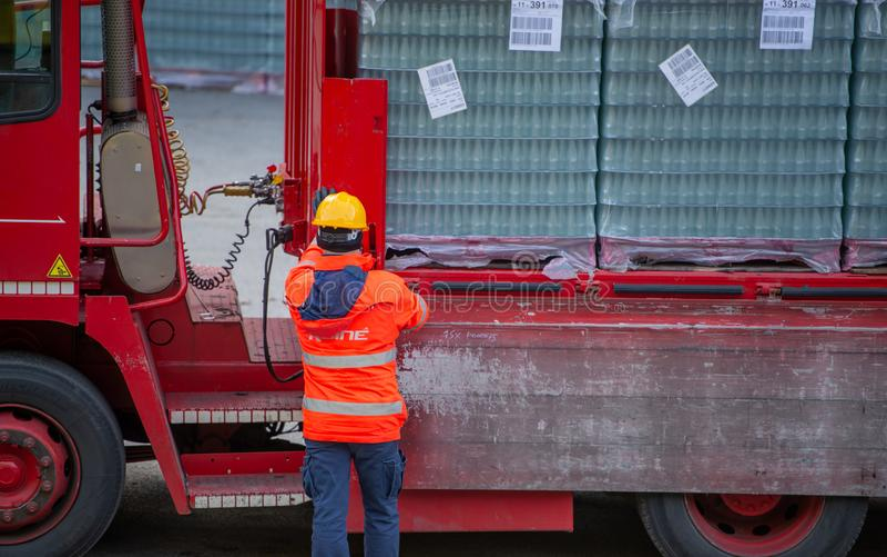 El conductor de camión asegura el cargamento de botellas de agua mineral atándolo con las cuerdas antes de comenzar el transporte imagen de archivo
