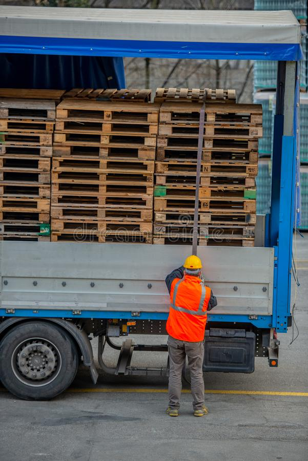 El conductor de camión asegura el cargamento de botellas de agua mineral atándolo con las cuerdas antes de comenzar el transporte imagen de archivo libre de regalías