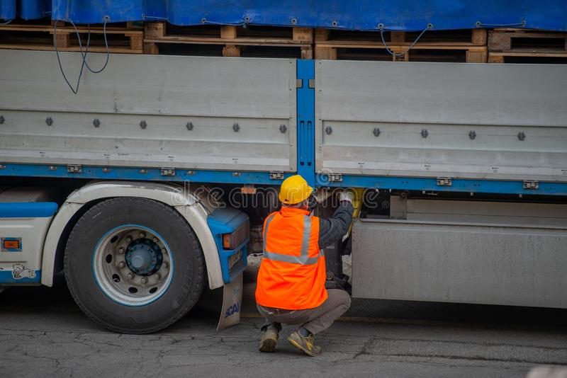 El conductor de camión asegura el cargamento de botellas de agua mineral atándolo con las cuerdas antes de comenzar el transporte imágenes de archivo libres de regalías