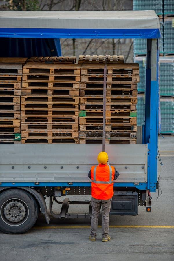 El conductor de camión asegura el cargamento de botellas de agua mineral atándolo con las cuerdas antes de comenzar el transporte foto de archivo