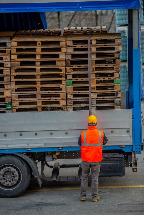 El conductor de camión asegura el cargamento de botellas de agua mineral atándolo con las cuerdas antes de comenzar el transporte imagenes de archivo