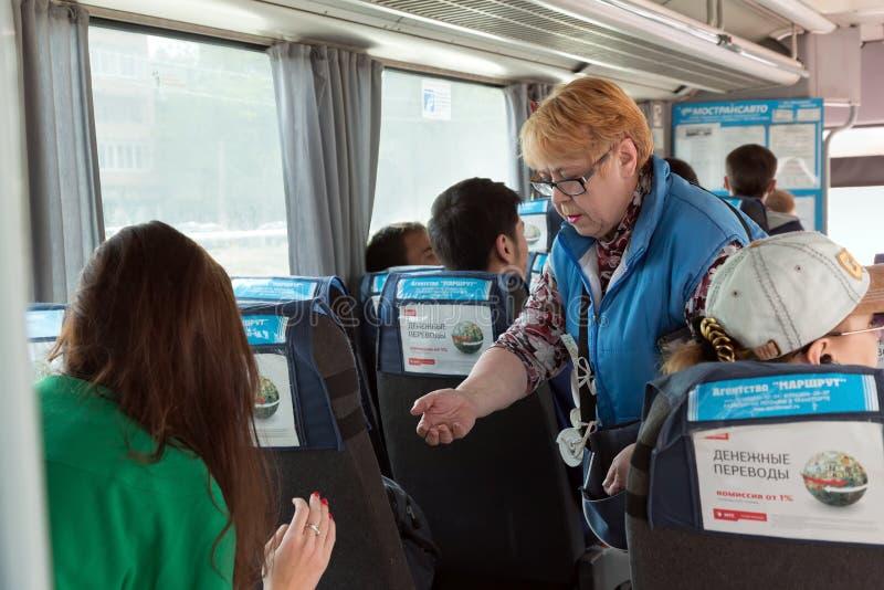 El conductor de un autobús del pasajero vende los boletos Rusia fotografía de archivo