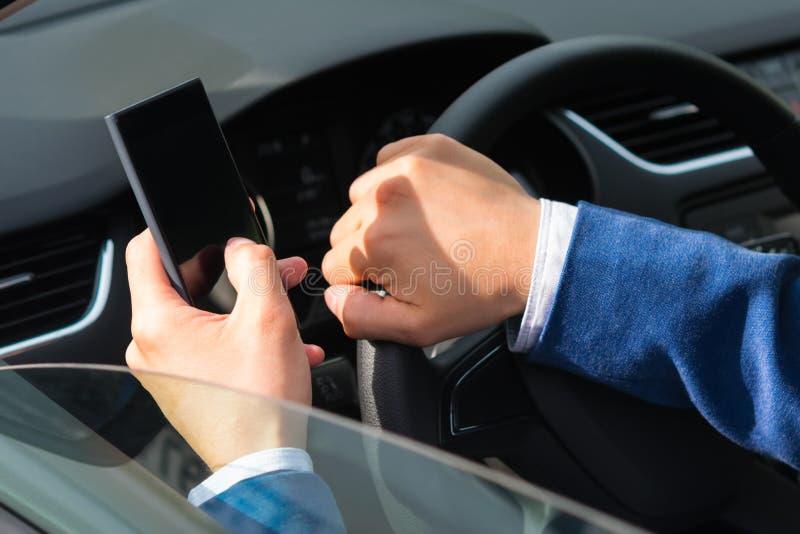 El conductor del coche utiliza el teléfono mientras que el coche se está moviendo, primer foto de archivo libre de regalías