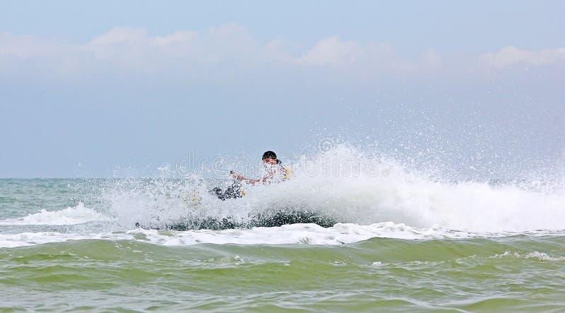 El conductor del esquí del jet da vuelta en el mar con una enorme cantidad de espray, el fondo se empaña imagenes de archivo
