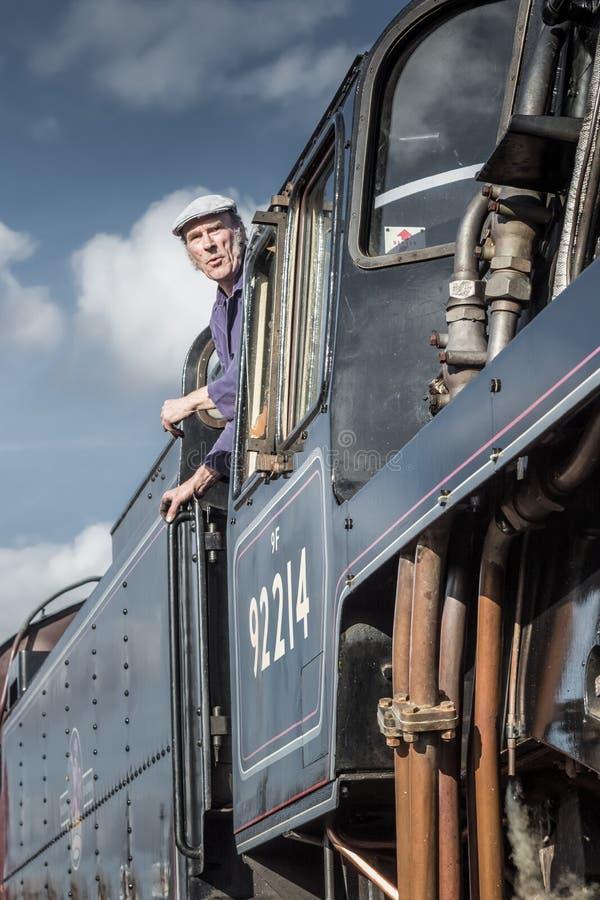 El conductor del tren del vapor mira fuera de su cabina imagenes de archivo