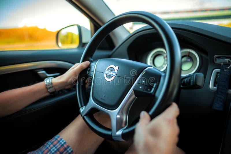 El conductor en pantalones cortos sostiene un volante de Volvo foto de archivo