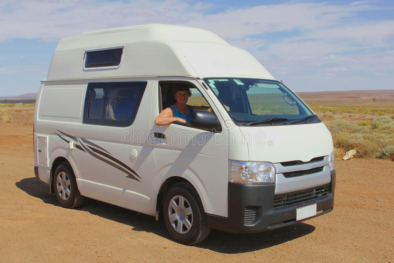 El conductor femenino está viajando en un vehículo recreativo en el desierto imagenes de archivo
