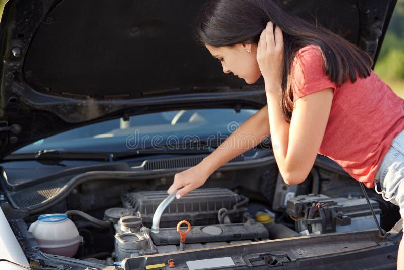 El conductor femenino profesional intenta reparar el coche, mira el motor, soportes cerca de la capilla abierta del auto, solucio imágenes de archivo libres de regalías