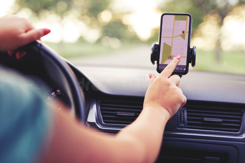 El conductor femenino utiliza la navegación en su teléfono móvil fotos de archivo