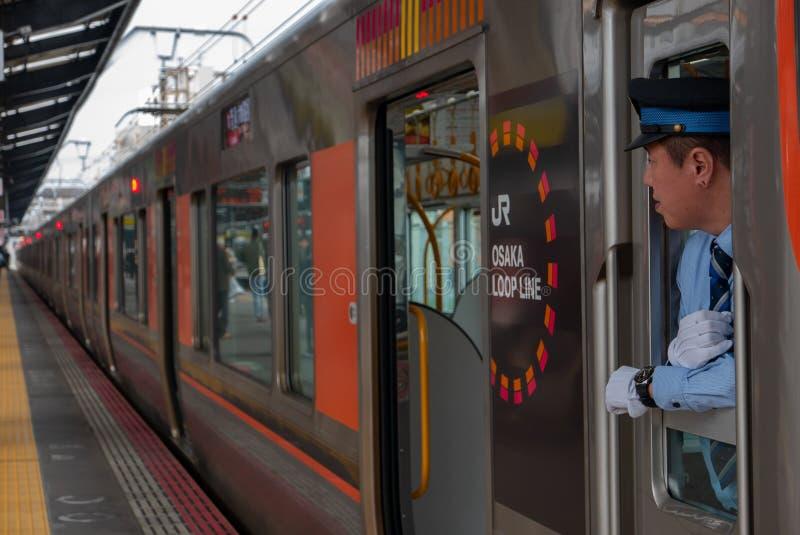 El conductor no identificado del tren busca a pasajeros en la estación de Shin-Imamiya en Osaka, Japón fotografía de archivo