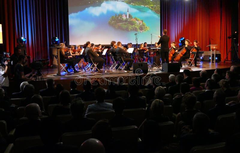 El conductor que dirigía a la orquesta sinfónica con los ejecutantes en fondo durante la ceremonia de inauguración del negocio sa imágenes de archivo libres de regalías