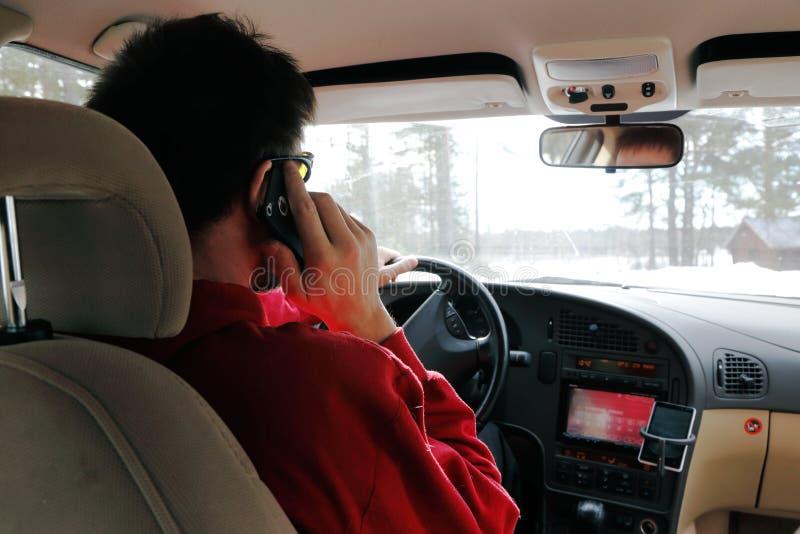 El conductor utiliza un teléfono celular fotografía de archivo libre de regalías