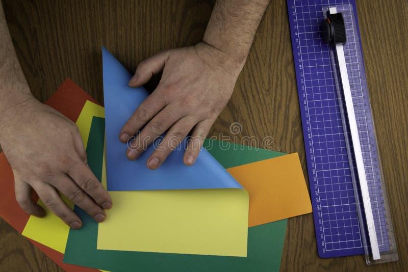 El conejito de papel para Pascua, manos hace la papiroflexia del papel coloreado, lección de la papiroflexia imagen de archivo