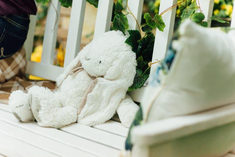 El conejo blanco del juguete miente en banco imagen de archivo