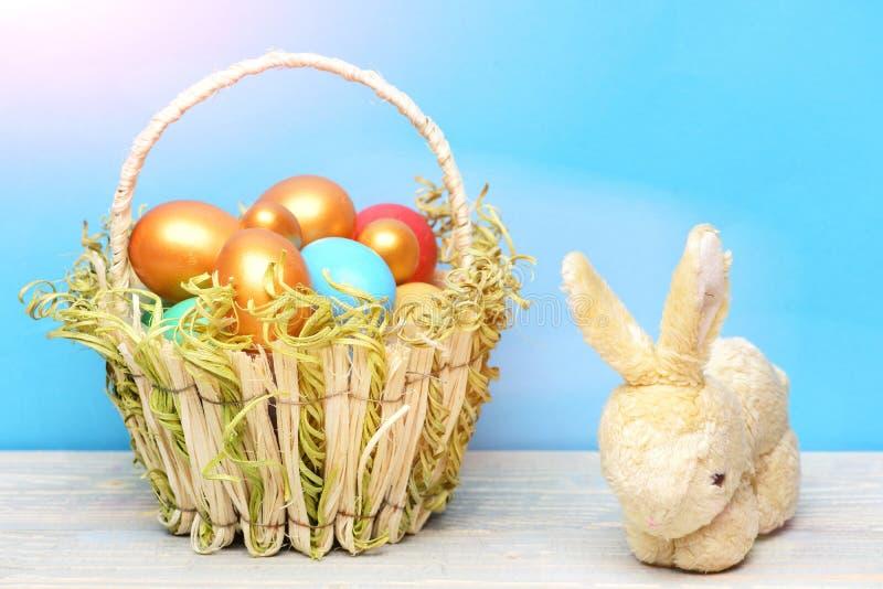 El conejo, liebre juega, el día de fiesta de pascua de la primavera, huevos coloridos en cesta imagenes de archivo